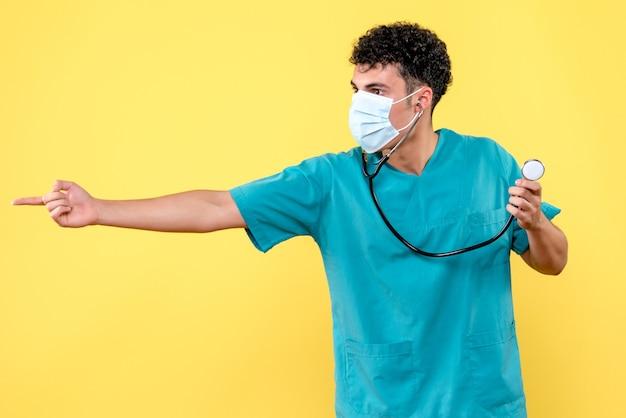 Vista frontale dottore il dottore in maschera con fonendoscopio indica di lato