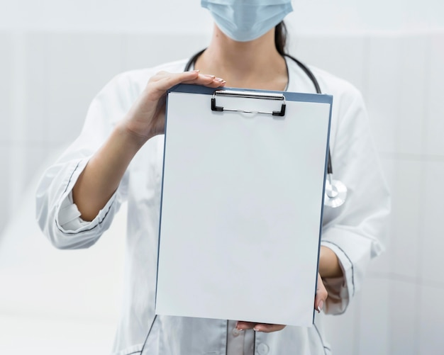 Front view doctor holding a blank clipboard