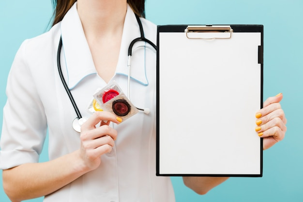 Front view doctor holding condoms and an empty clipboard