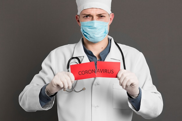 Front view of doctor holding torn paper with coronavirus
