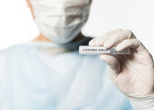 Front view of doctor holding tube with coronavirus