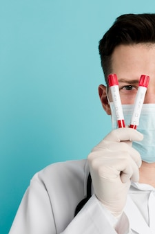Front view of doctor holding up vacutainers
