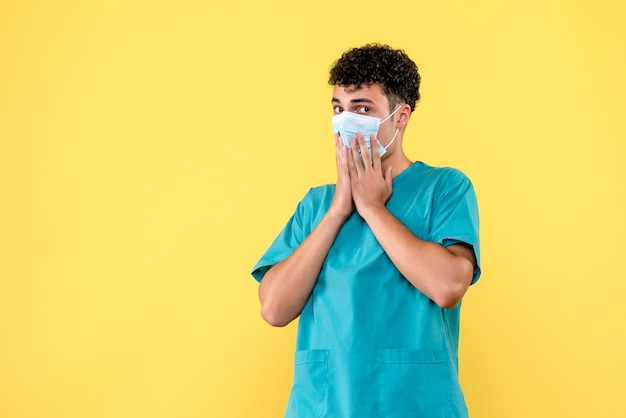 正面の医者マスクをした医者はコロナウイルスの検査結果に驚いています