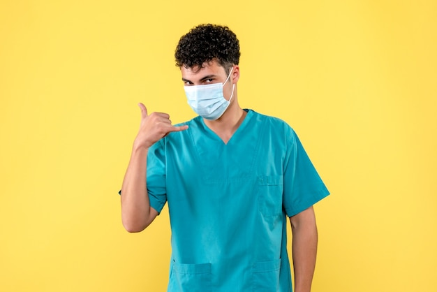 正面の医者マスクをした医者はあなたが頭痛を持っているなら救急車を呼ぶように言います