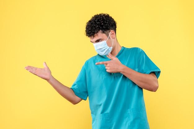 正面の医者マスクをした医者は人々にマスクを着用するように促します