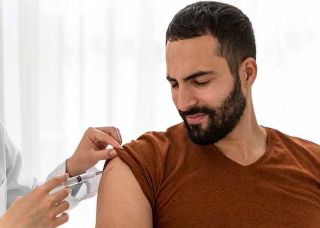 Front view doctor vaccinating a bearded man