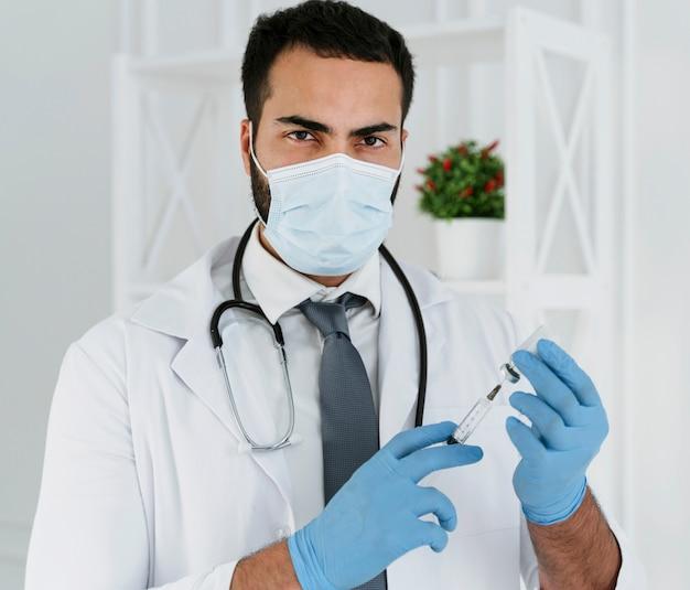 注射器を保持している医療マスクを持つ正面図の医師