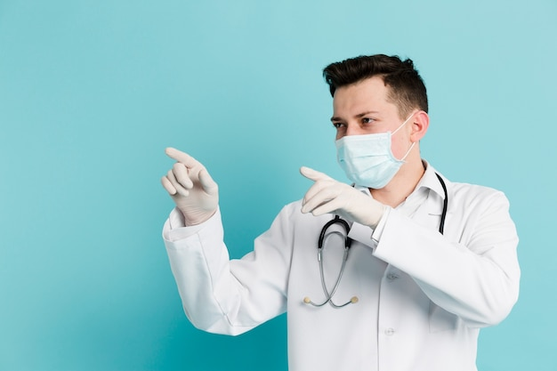 Front view of doctor with medical mask pointing while wearing surgical gloves