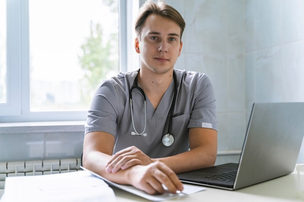 Front view of doctor with stethoscope working on laptop