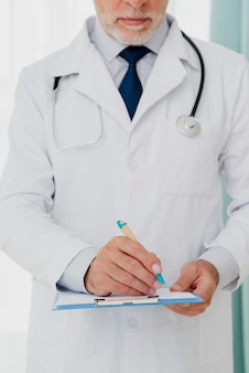 Front view of doctor writing on clipboard