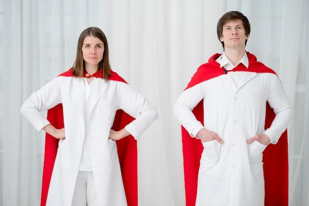 Vista frontale medici in posa con mantelle