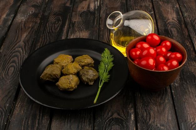 Dolma vista frontale all'interno della banda nera con pomodorini rossi freschi e olio d'oliva sul pavimento rustico in legno marrone
