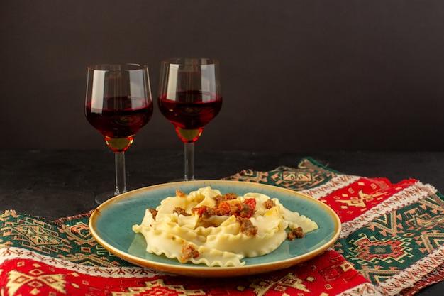 Una pasta con vista frontale cucinata gustosa salata all'interno di un piatto verde rotondo con bicchieri di vino sul tappeto progettato e sulla scrivania scura