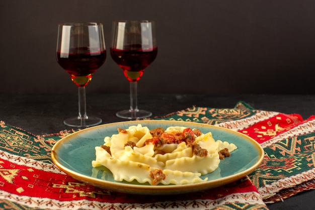 A front view dough pasta cooked tasty salted inside round green plate with glasses of wine on designed carpet and dark desk