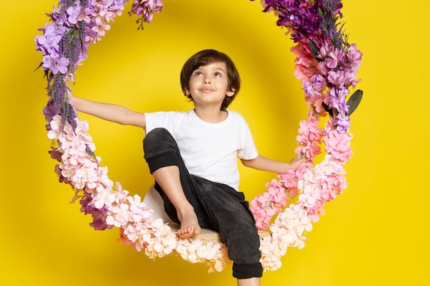 A front view dreaming cute boy in white t-shirt around flower stand on the yellow desk