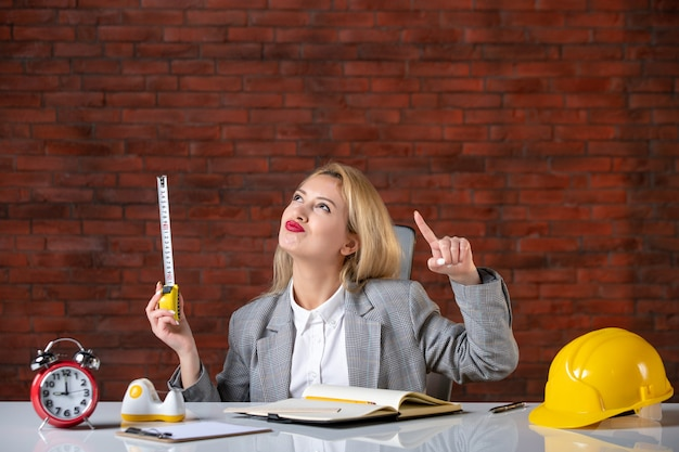 彼女の職場の後ろに座っている女性エンジニアを夢見ている正面図