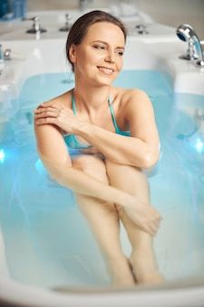 Front view of a dreamy beautiful young caucasian woman in a hydromassage bathtub looking away