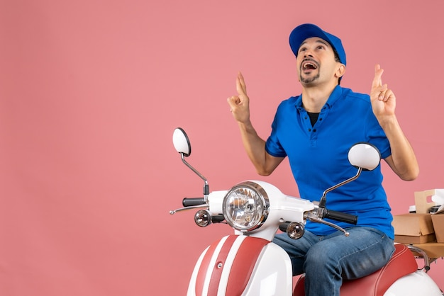 Front view of dreamy courier guy wearing hat sitting on scooter on pastel peach background