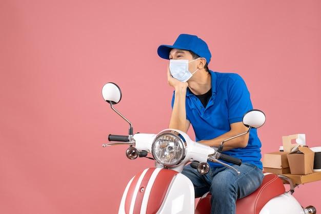 Vista frontale del corriere sognante in maschera medica che indossa un cappello seduto su uno scooter su sfondo color pesca pastello