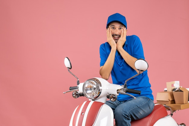 Front view of dreamy delivery guy wearing hat sitting on scooter on pastel peach background