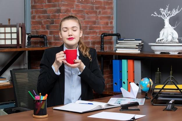 Vista frontale di una giovane donna sognante seduta a un tavolo e con in mano una tazza rossa in ufficio