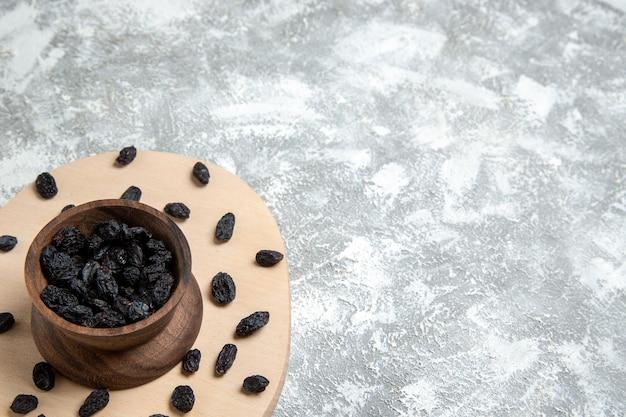 Вид спереди сушеный черный изюм на белом пространстве