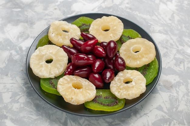 Vista frontale anelli di ananas frutta secca e fette di kiwi su superficie bianca