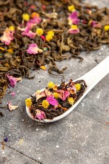Vista frontale tè fruttato essiccato fresco con sapore di fiori su uno spazio grigio
