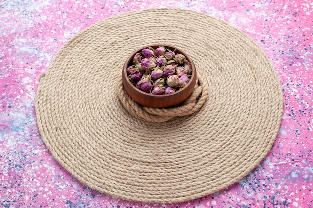 Vista frontale fiori piccoli secchi con corde sulla scrivania rosa. sfondo di foto a colori di fiori.