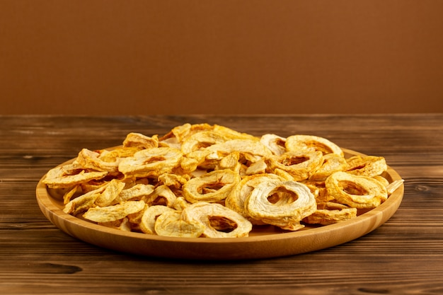 A front view dried pineapple rings inside brown desk sour sweet tasted on the brown background fruits dry product