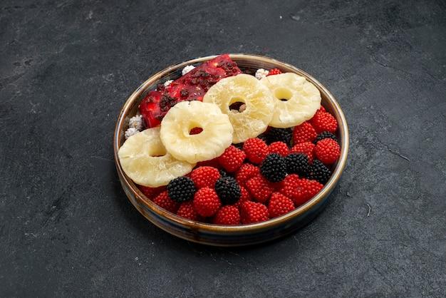Vista frontale anelli di ananas essiccati con bacche di confettura su superficie grigio scuro frutta secca uva passa dolce zucchero candito foto