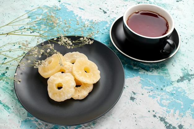 Вид спереди сушеные кольца ананаса с чашкой чая на синей поверхности