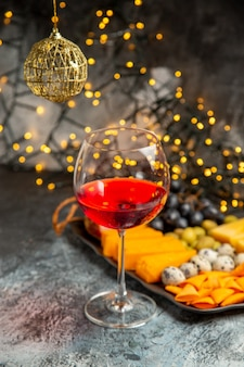 Vista frontale del vino rosso secco in un bicchiere accanto a uno spuntino su sfondo grigio