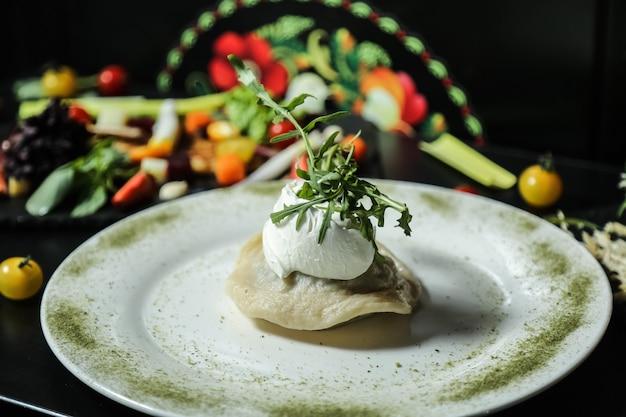Вид спереди клецки со сметаной и рукколой на тарелке со специями