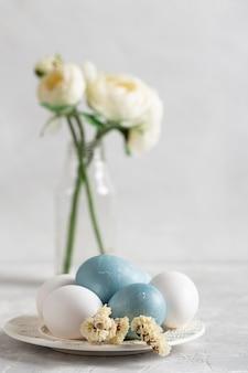 Vista frontale delle uova di pasqua sul piatto con i fiori in vaso