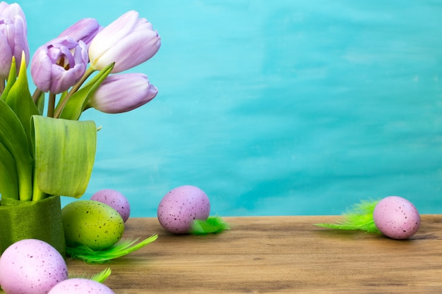 Front view of a easter eggs with green feathers, purple tulips on wood and turquoise background with message space.