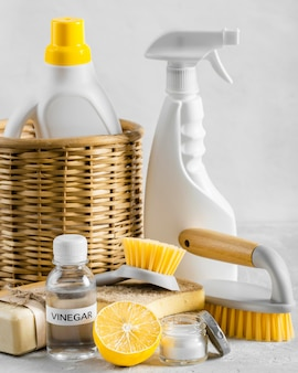 Front view of eco-friendly cleaning brushes in basket with lemon and vinegar