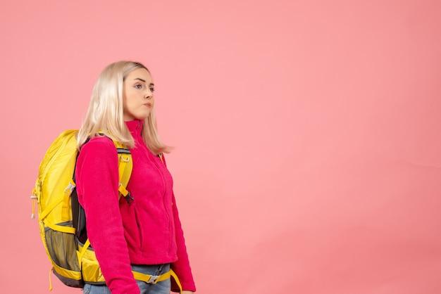 Donna di viaggiatore tagliente vista frontale con zaino in piedi sulla parete rosa