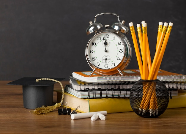 Front view education day arrangement on a table with a clock