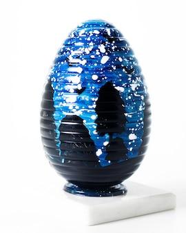 Vista frontale uovo blu-nero progettato sul pavimento bianco