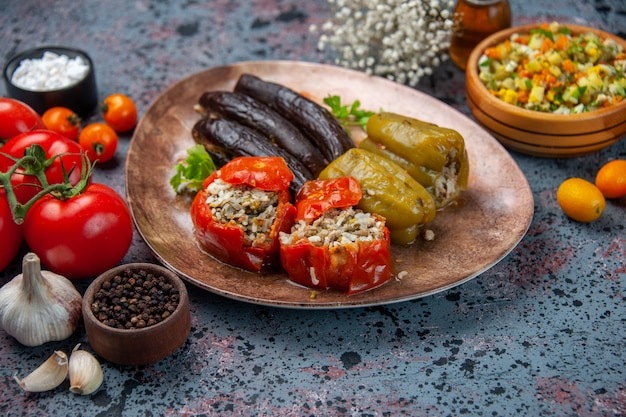 Баклажанная долма с вареными помидорами и болгарским перцем, начиненная мясным фаршем, внутри тарелки на синем фоне, вид спереди