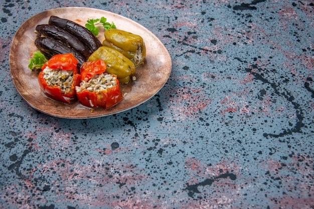 파란색 배경에 접시 안에 다진 고기로 가득 요리 토마토와 벨 고추 전면보기 가지 돌마