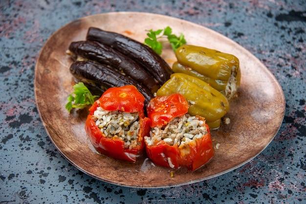 青の背景のプレートの内側にひき肉で満たされた調理済みトマトとピーマンの正面図ナスドルマ