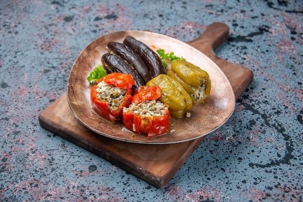 Долма из баклажанов с вареными помидорами и болгарским перцем, вид спереди, фаршированная мясным фаршем, на синем фоне