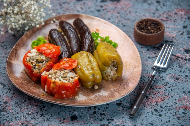 Front view eggplant dolma with cooked tomatoes and bell-peppers filled with ground meat inside plate on blue background food dish color dinner meal