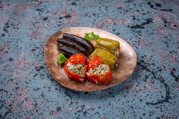 Vista frontale dolma di melanzane con pomodori cotti e peperoni ripieni di carne macinata all'interno della piastra su sfondo blu