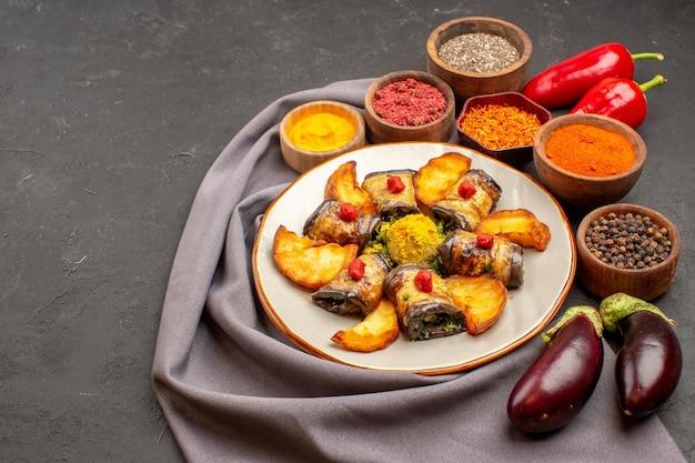Involtini di melanzane vista frontale piatto cotto con patate al forno e condimenti su spazio buio dark