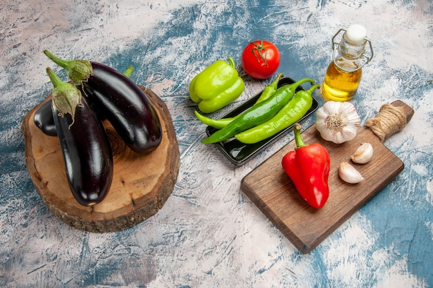 Front view eggplants on tree wood board hot peppers on black plate tomato red pepper garlic on chopping board eggplant on blue-white background