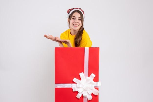 Вид спереди приподнятая милая девушка в шляпе санта-клауса, стоящая за большим рождественским подарком