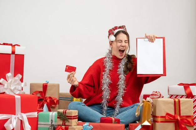 선물 주위에 앉아 카드와 문서를 들고 산타 모자와 전면보기 의기 양양 소녀